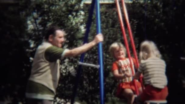 Opa beaufsichtigt Schaukel mit Kindern