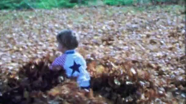 Boy runs in autumn leaves pile