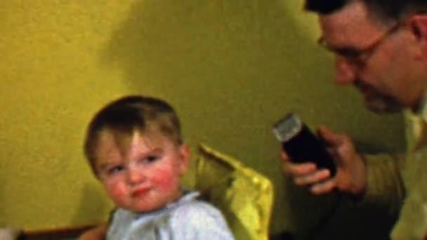 Papa schneidet Babyhaare mit elektrischen Summer-Rasuren