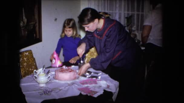 a woman cutting a birthday cake with child
