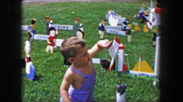 boy playing with yard handmade windmills