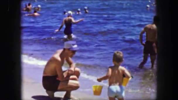 Dad proudly watching as toddler son plays on beach