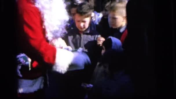 Santa a paní claus rozdávání candy hole pro děti