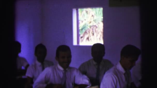 boys and girls in uniforms sitting in classroom