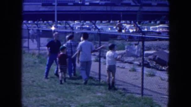 children walking along side a chainlink fence
