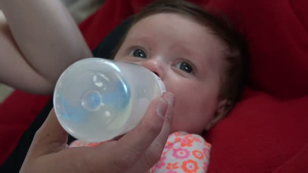 Baby drinks a milk from bottle