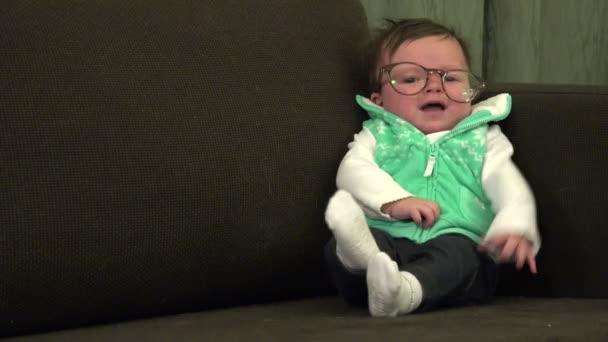 Dítě sedí na gauči s brýlemi