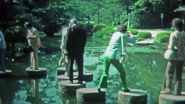 Lidé chodí rybník japonském stylu zen odrazovým můstkem
