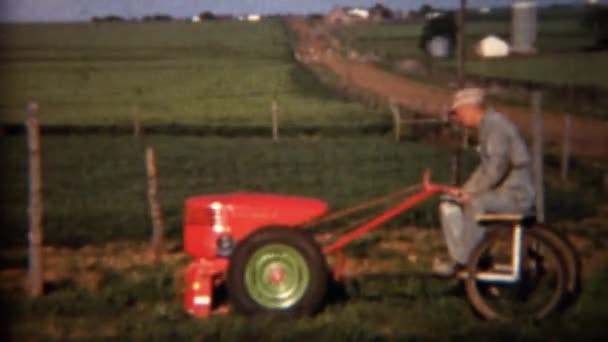 Mann fährt schweren Rasenmäher und mäht das Gras