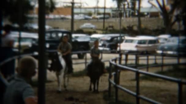 Děti jezdící koně na oploceném stopa