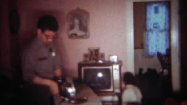 Táta žehličky oblečení, zatímco dcera sedí pár centimetrů od televize