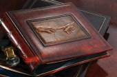 Photo Leather photo album on expensive wooden with a reproduction of da Vinci on the table