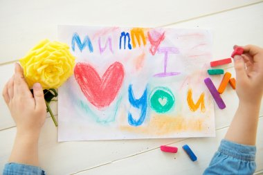 Little Girl is Drawing Postcard for Mothers Day