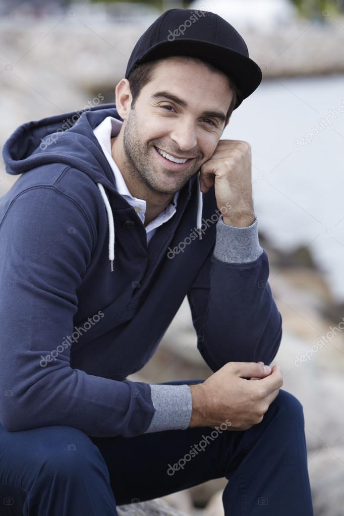Portrait of mid adult man in cap and hooded top smiling — Photo by sanneberg a49080b289f1
