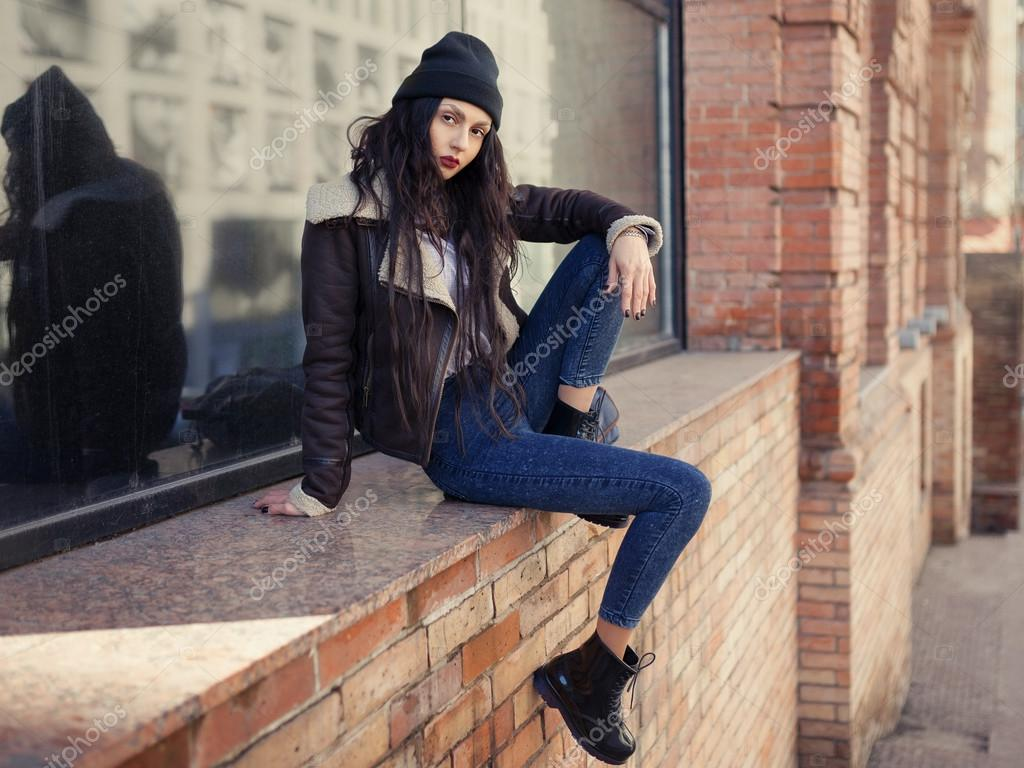 Outdoor lifestyle fashion portrait of pretty young girl, wearing in hipster  swag grunge style on urban background. Wearing hat and jeans.