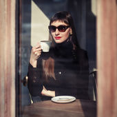 Young fashion woman sitting in cafe on the street with cup of cappuccino. Outdoors portrait in retro style