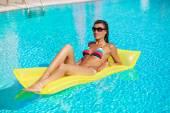 Portrét krásné opálené ženy relaxační v bazénu v pruhované plavky s žlutou nafukovací matrace. Kreativní gel polský, manikúru a pedikúru. Horký letní den a jasné slunečné světlo