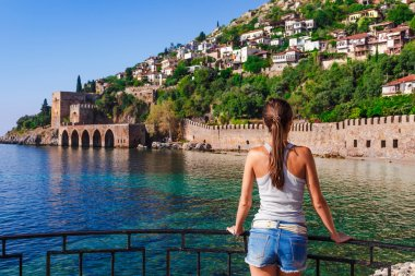 Young woman look on ancient shipyard near of Kizil Kule tower in Alanya peninsula, Antalya district, Turkey, Asia. Famous tourist destination with high mountains. Part of ancient old Castle. Summer br