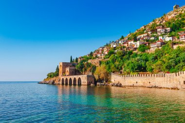 Landscape of ancient shipyard near of Kizil Kule tower in Alanya peninsula, Antalya district, Turkey, Asia. Famous tourist destination with high mountains. Part of ancient old Castle. Summer bright da