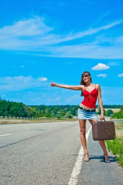 Beautiful young girl or woman in mini with suitcase hitchhiking along a road