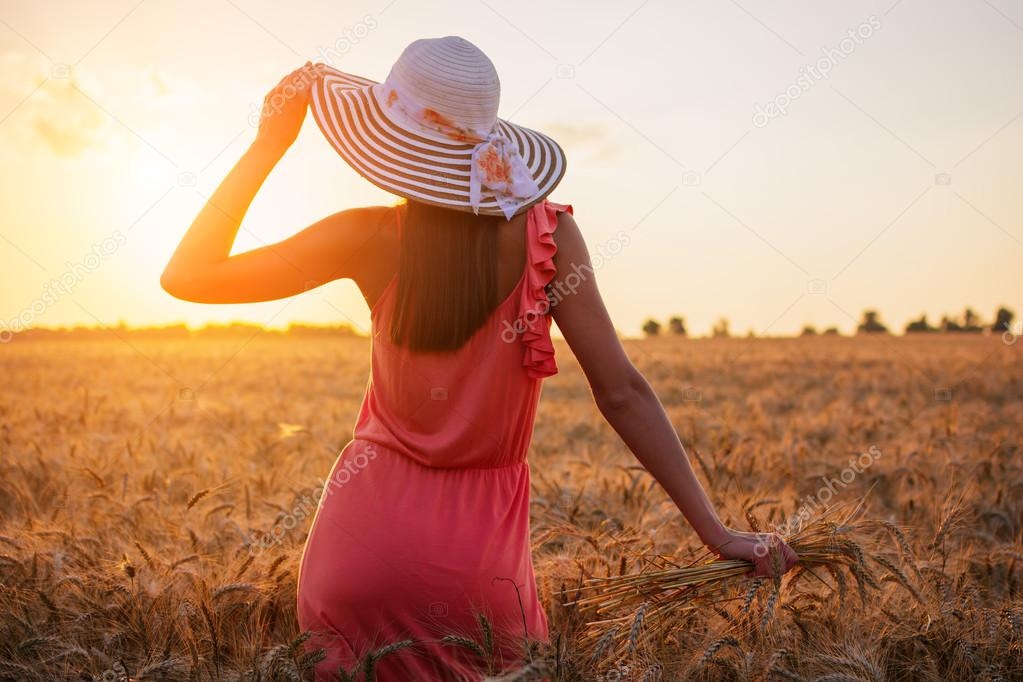 Beautiful young woman with brown hear wearing rose dress and hat enjoying outdoors looking to the sun on perfect wheat field on sunset