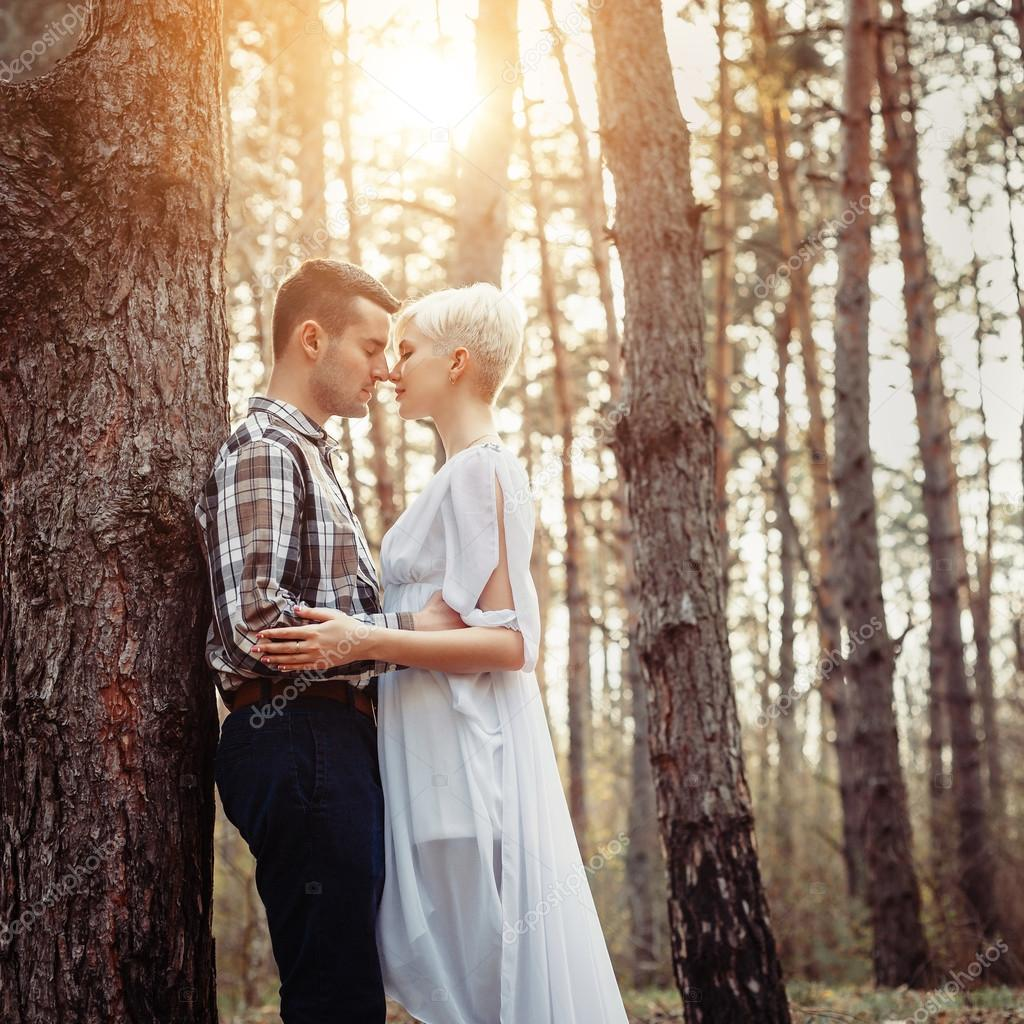 Фотообои Outdoor lifestyle portrait of young couple hugging in pine forest. Sunny warm weather. Backlight and sun. Retro vintage toned image, film simulation.