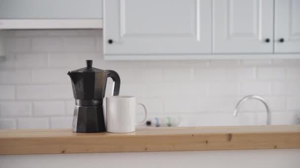 Pohled zepředu na konvici na kávu a šálek kávy na kuchyňské lince.