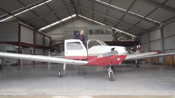 Letový instruktor vchází do hangáru, zavírá dveře a připravuje se k letu..