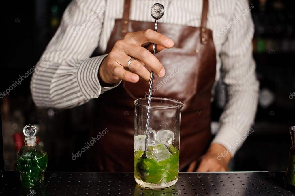 Bartender is stirring cocktails on the bar counter