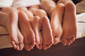 Photo close up of a family showing off their feet under the covers.