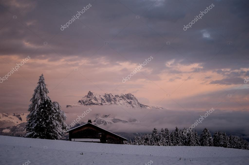Winter sunset with a log cabin,