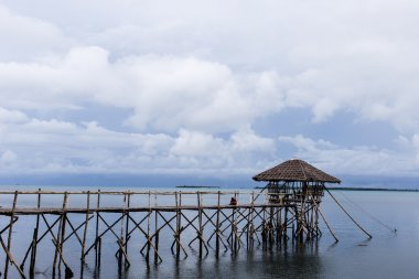 Wooden house is on the pier that goes into the sea on the island of Palawan in the Philippines