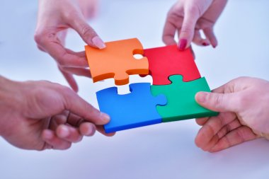 business people assembling jigsaw