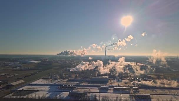 Luftaufnahme von Fabriken mit dickem Smog aus Rohren im Sonnenlicht.