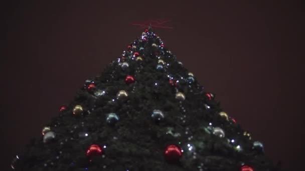 közeli kép egy karácsonyfa fények villog az éjszaka odakint.
