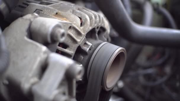 The car engine is running. Close-up of the engine turning.