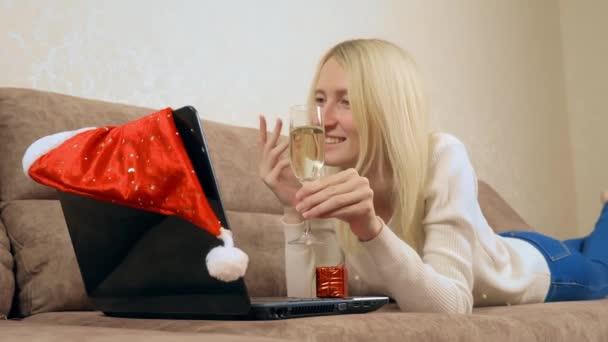 Die Blondine kommuniziert per Laptop mit Verwandten oder Freunden.
