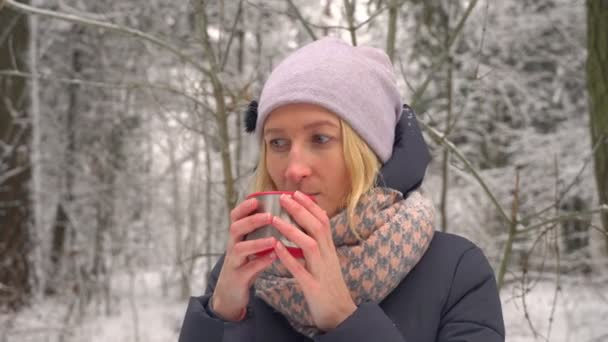young woman drinking hot drink. Steam from hot coffee or tea. Winter camping.