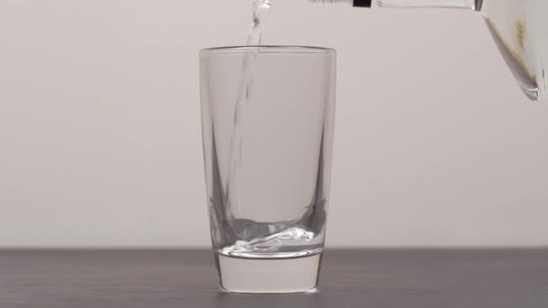 Barman nalévá do sklenic vodku nebo tequilu