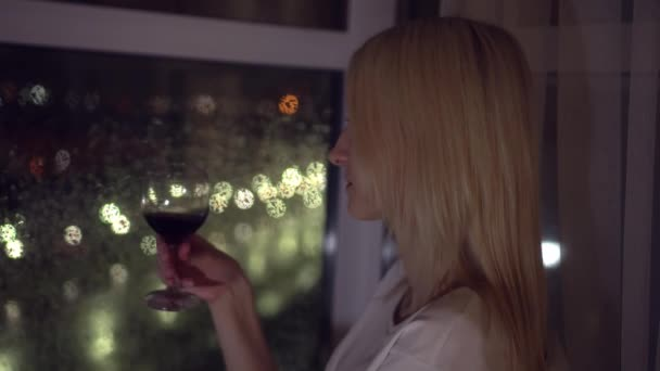against the background of the night city, a woman holds a glass of wine.