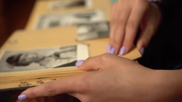 mladá žena prohlíží rodinné album se starými černobílými fotografiemi