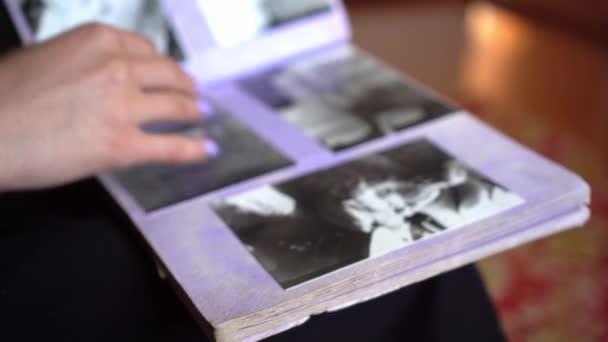 Žena se dívá na staré fotoalbum doma.
