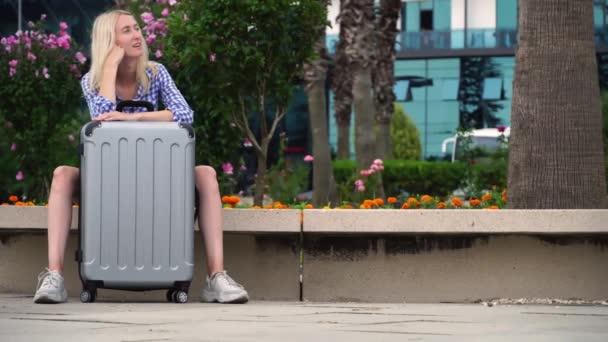 Hezká žena s šedým kufříkem čeká na služební let poblíž letiště.