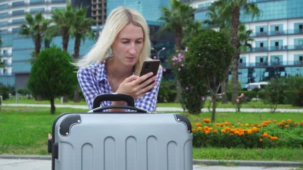 Eine hübsche Frau mit grauem Koffer sitzt auf einer Parkbank. ein Smartphone.