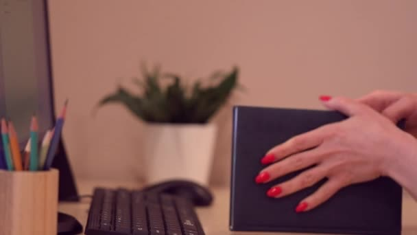 A woman writes in a diary with a pencil on the desktop. The idea of time management, working day
