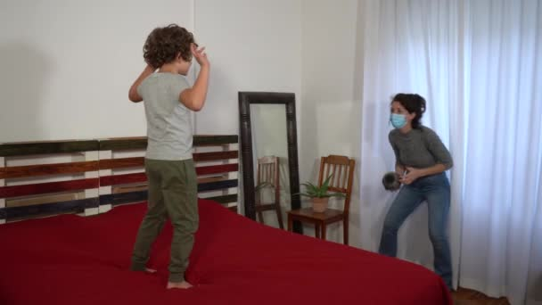 Boy playing football with mother in room during covid