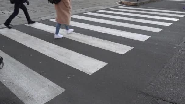 Európa, Olaszország, Milánó 2021. január - fekete hátterű fehér gyalogos átkelés - gyalogosok áthaladása egy városátkelőhelyen és a közlekedés szennyezése
