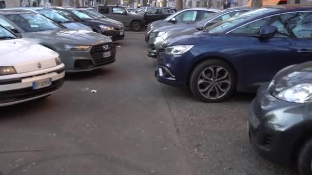 Itálie, Miláno leden 2021 - parkoviště plné aut zaparkovaných v herringbone vzoru ve Viale Papiniano - znečištění ovzduší a dopravní automobily během Covid-19 Coronavirus výluky