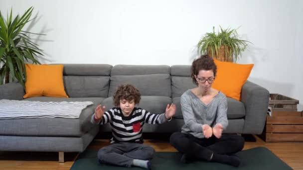 Happy legrační a bláznivá rodina v bytě, matka a syn dělá jóga meditační tělocvična během Covid-19 Coronavirus uzamčení karantény doma - životní styl v obývacím pokoji