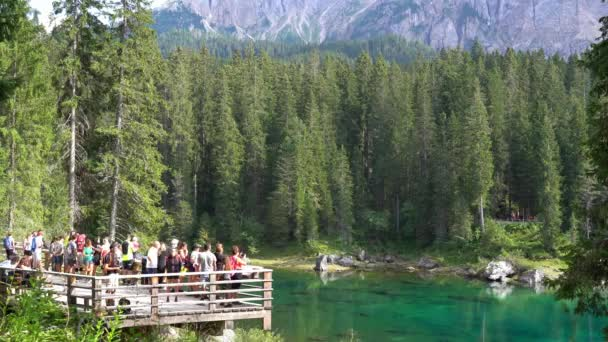 Europe, Italy , Trentino August 2021 - Tourist visiting Lago di Carezza (Karersee Lake) in Dolomites Catinaccio Mountains - Green clear water and pine wood